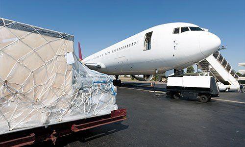 pista d'atterraggio con sulla sinistra una piattaforma di carico e davanti un aereo con il portellone aperto che aspetta il carico