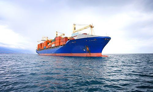 una nave a righe di color bianco, blu e rosso carica di container rossi, bianchi e blu in mezzo al mare