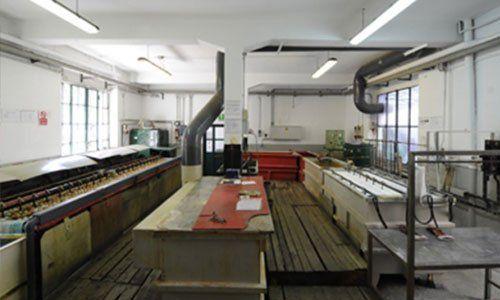 interno di un' industria di cromature con banchi di lavori in legno e tubature di macchine industriali a Milano