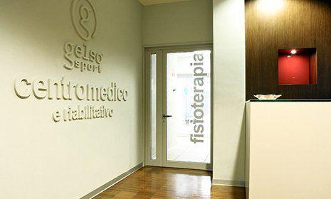 bancone della reception, con scritta Gelsosport centromedico e riabilitativo su un muro sul lato sinistro della sala a Rimini