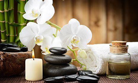 orchidee bianche, candele bianche, olio di essenza in un barattolo e dei sassi uno sopra l'altro