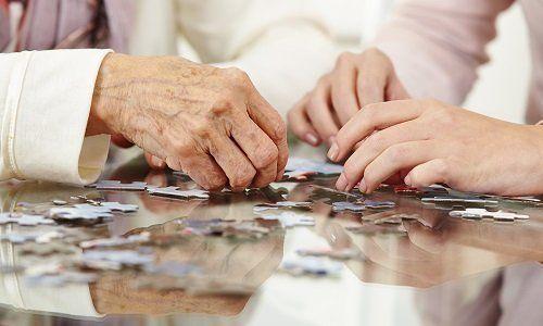 delle mani di alcuni signore anziane con dei pezzi di puzzle