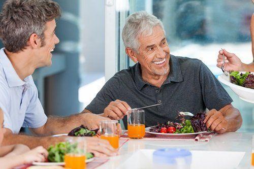 due signori al tavolo sorridenti  con dei piatti di verdura