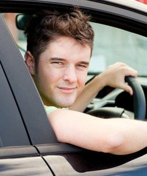 a man holding the steering wheel with one hand