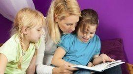una donna e una bambina che leggono un libro è accanto un'altra bambina bionda