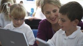 due bambini al computer e accanto a loro una donna sorridente