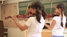 delle bambine che suonano il violino