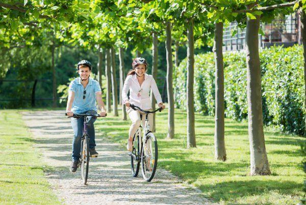 Un ragazzo e una ragazza in bicicletta in un viale