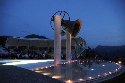 Due colonne in cemento che reggono una campana, a terra delle luci e degli spalti con delle persone