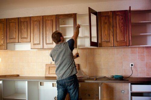 un uomo che monta un' anta di un mobile cucina