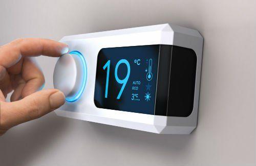 una mano che regola un termostato