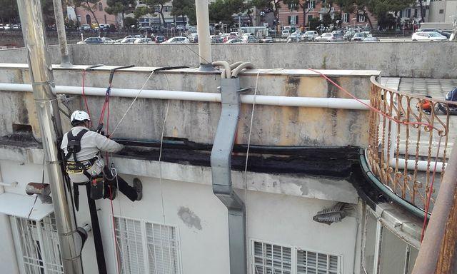 un muratore mette materiale impermeabile sul tetto