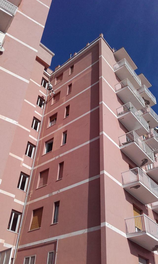 Il muratore si cala dal tetto di un palazzo