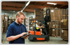 Man holding a clip board with a forklift truck in the background