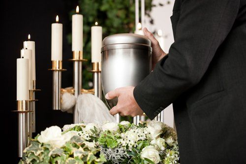 uomo tocca un vaso cinerario vicino a delle candele accese