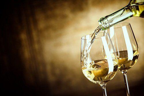 una bottiglia che versa del vino bianco in due bicchieri
