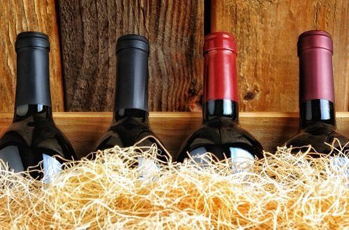 quattro bottiglie di vino in contenitore di legno con paglia