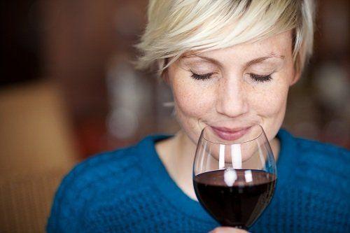 una donna che degusta un bicchiere di vino rosso