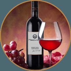 Primo piano di una bottiglia, un bicchiere di vino rosso e dell'uva