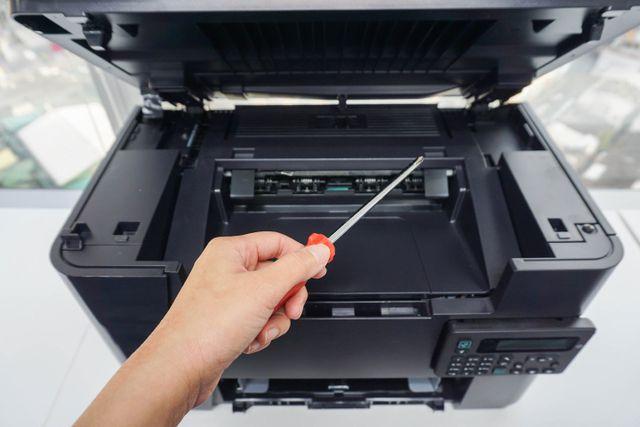 tecnico con cacciavite per riparare fotocopiatrice