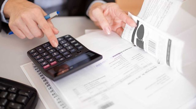Employees discussing bookkeeping document in St. Charles