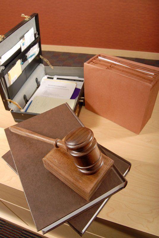 un martello delle udienze,dei libri un raccoglitore e una valigetta aperta
