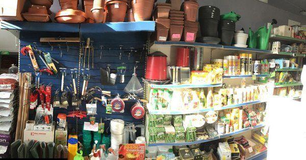 scaffale con attrezzi da giardino, vasi, cesoie, stivali, ecc..