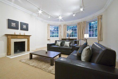 Soggiorno curvo, due sofá grigio scuro, tavolino di legno e camino