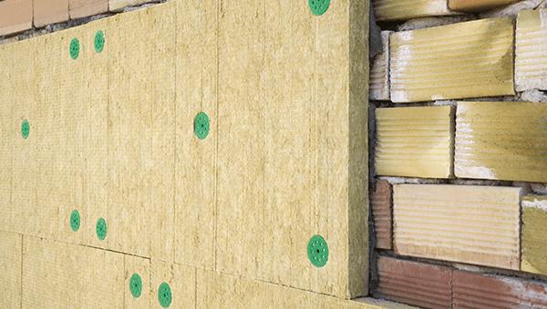 dei pannelli isolanti su un muro e accanto dei mattoni a vista