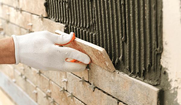 una mano con un guanto bianco e arancione che posiziona dei mattoni su del cemento fresco