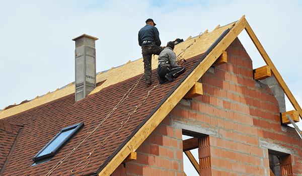 degli operai al lavoro su un tetto di una casa in ristrutturazione