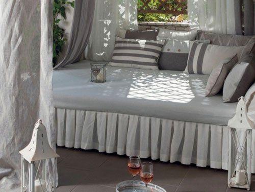 Un letto a baldacchino con tanti cuscini