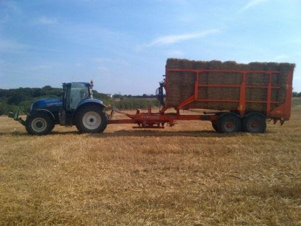 tractor towing bales of hay on trailer