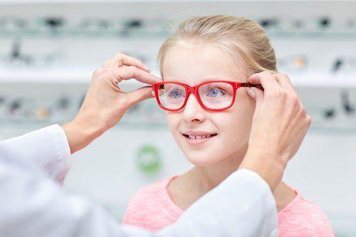 due mani di un'ottica che mettono un paio di occhiali da vista rossi a una bambina bionda