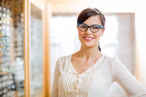 una ragazza con un paio di occhiali da vista di color blu