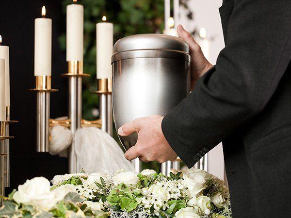 Un candelabro e un uomo con un'urna in mano