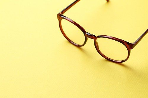 occhiali dal marco rosso appoggiati su un piano giallo