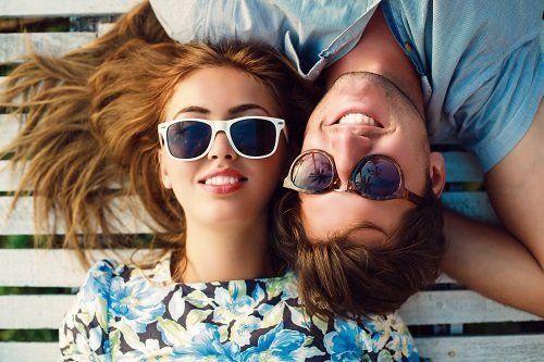 una ragazza e un ragazzo sdraiati che indossano degli occhiali da sole