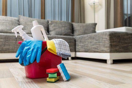un secchio con dei guanti, stracci, spugne e prodotti di pulizia