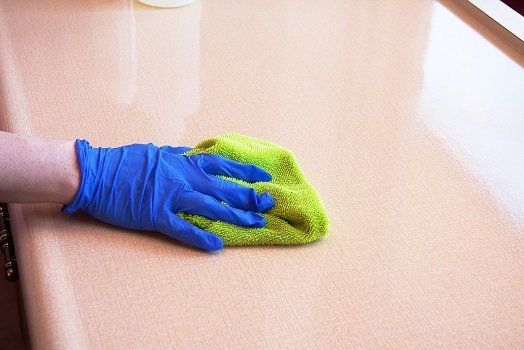 una mano con un guanto blu e un panno in microfibra verde