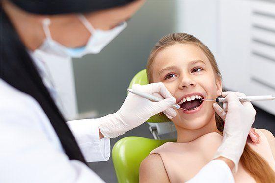 Dentist examining girls teeth in the dentists chair