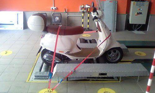 scooter di color bianco legato con delle cinghie sul ponteggio