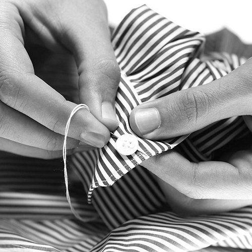 due mani che cuciono un bottone di una camicia