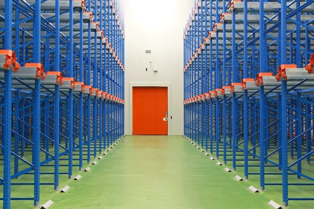 Warehouse interior with orange door and blue shelves