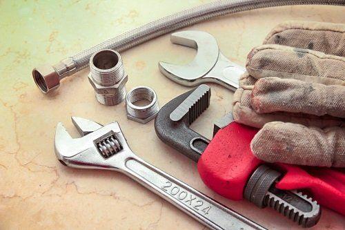 Guanti di lavoro, chiave inglese, dadi e tubo di connessione