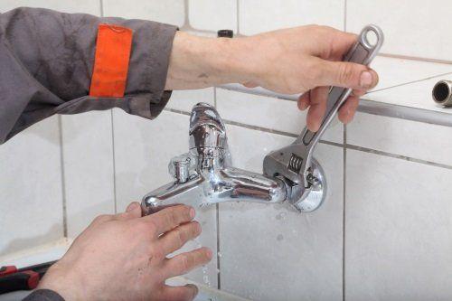 un idraulico aggiusta un rubinetto