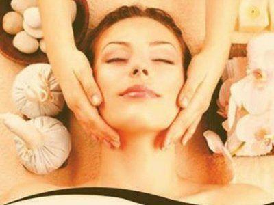 mani massaggiano viso di giovane donna