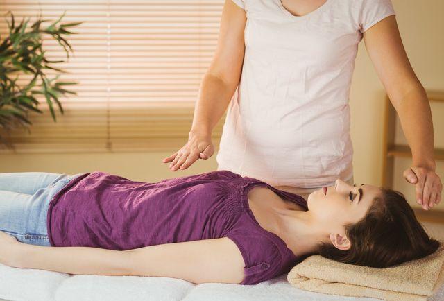 donna su lettino durante trattamento reiki