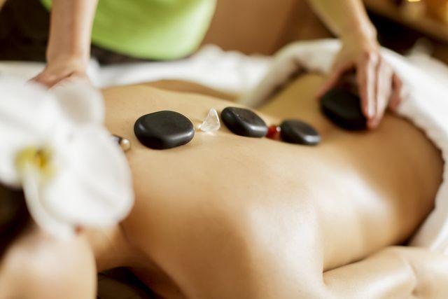 massaggiatrice esegue massaggio hot stone
