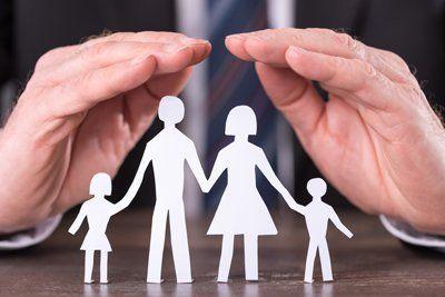 Delle mani sopra una famiglia di carta